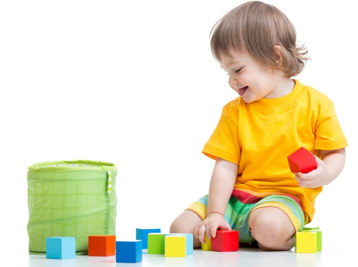child putting colorful blocks into a container