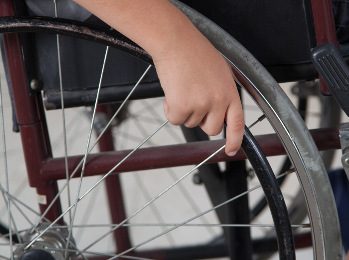 kid's hand on wheelchair