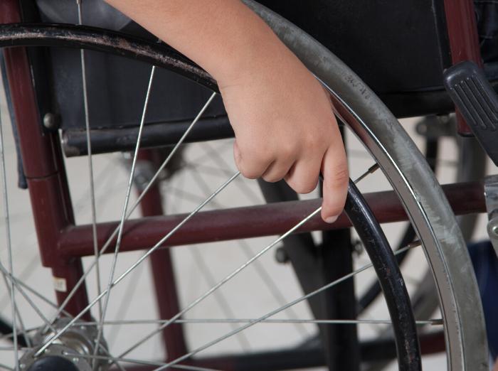 kid's hand on wheelchair