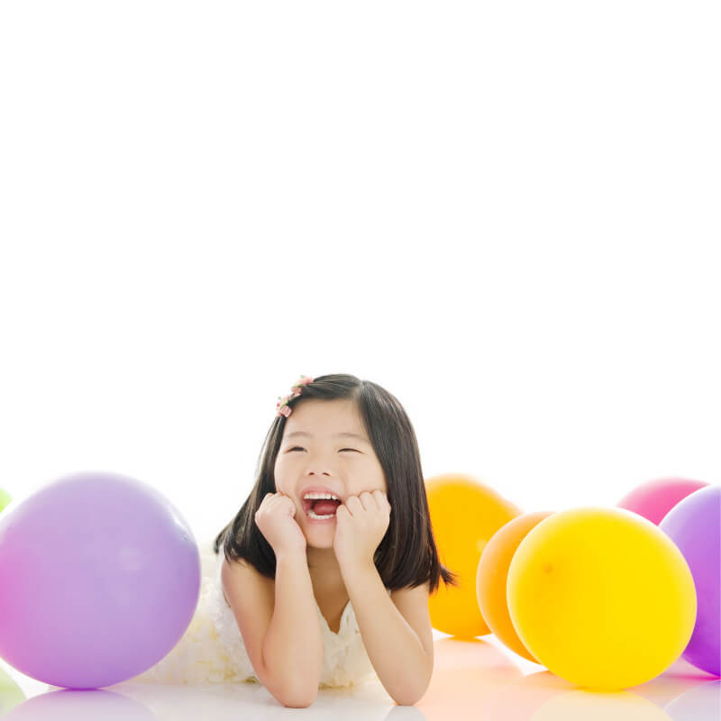 little girl smiling with balloons
